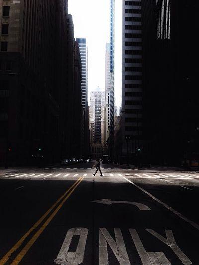 Man walking on city street against cityscape