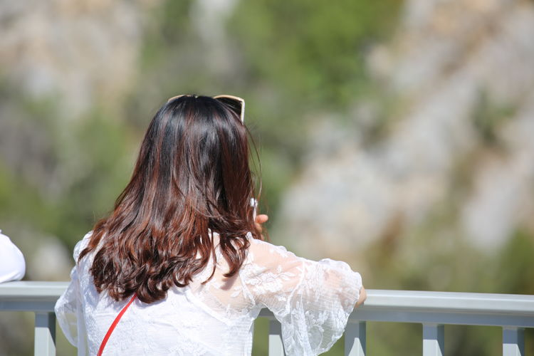 Rear view of young woman standing by railing in balcony