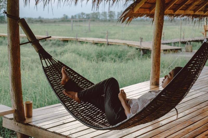 Woman Lying In Hammock At Porch