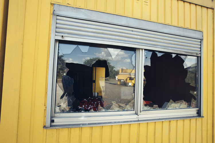 smashed glass windows on a cash cottage Construction Site Crime Shutters Abadoned Accident Broken Building Site Cash Cottage Concept Cracked Criminal Crushed Damaged Demolished Destroyed Fragility Glass Impact No People Pieces Robbery Shattered Vandalism Window Yellow