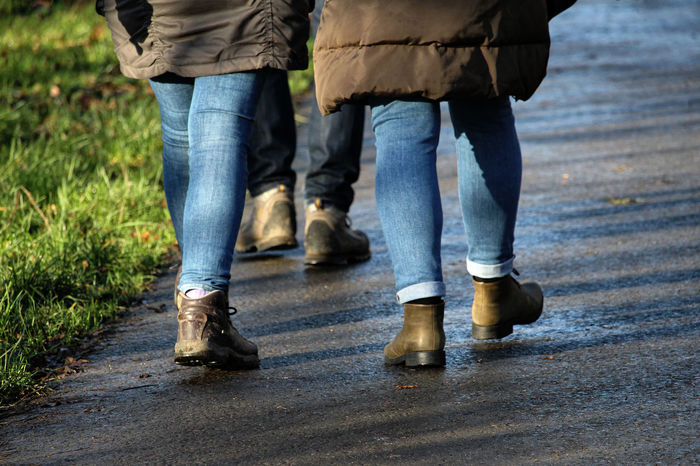 The Boots. Adult Body Part Bonding Casual Clothing Day Human Body Part Human Foot Human Leg Human Limb Jeans Leisure Activity Lifestyles Low Section Men Outdoors People Real People Three People Togetherness Walking Walking Boots Women