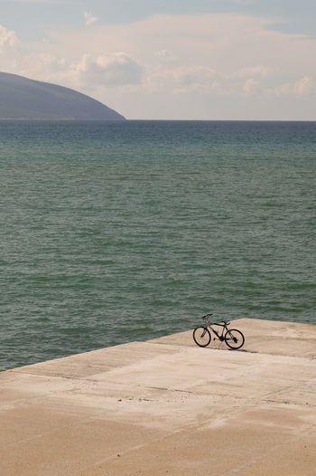 Bicycle on a pier next to the sea Bicycle Blue Clouds And Sky Day Gray No People Outdoors Pier Sea Sea And Sky Seaside Sky Travel Travel Photography Water Waves