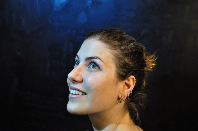 Headshot Portrait Young Adult Smiling One Person Young Women Looking Beauty Looking Away Beautiful Woman Women Indoors  Happiness Adult Real People Lifestyles Leisure Activity Hair Side View Hairstyle Black Background Contemplation