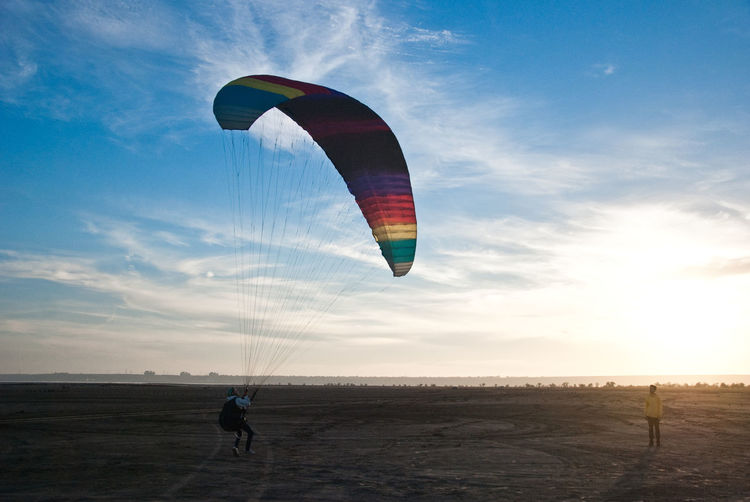 Sky Adventure Parachute Leisure Activity Paragliding Extreme Sports Land Flying Cloud - Sky Lifestyles One Person Real People Unrecognizable Person Horizon Nature Freedom Mid-air Environment Sport Beauty In Nature Outdoors Horizon Over Water
