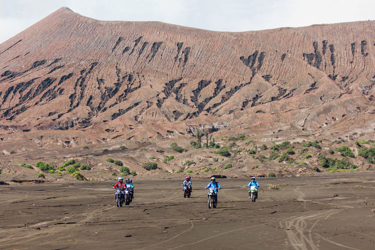 Group of off road motor bikers ride across the ash flats of Mt Bromo, Java, Indonesia. Adventure Bromo Cross Country Expedition Exploring Flat Land Friends Gang Group INDONESIA Java Motorbike Mt Bromo Off Roading Riders Riding Sand Flats Volcanic  Volcanic Landscape Volcano