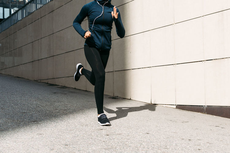 Low Section Of Woman Jogging On Footpath By Wall