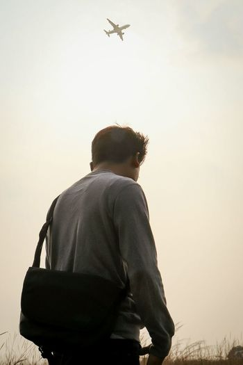 Rear view of man looking at airplane against sky