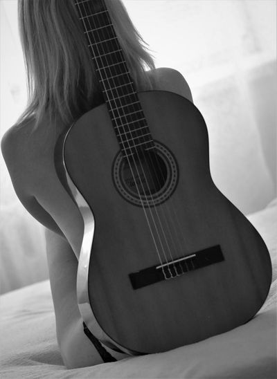 Woman sitting on guitar at home