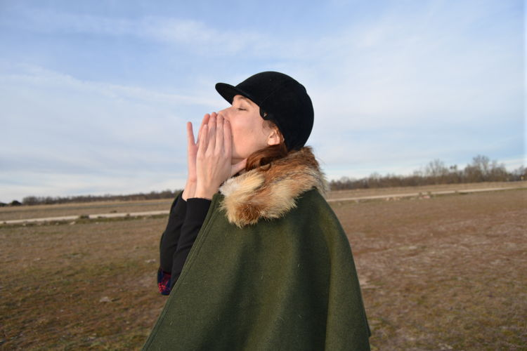 Side view of woman screaming while standing on field against sky