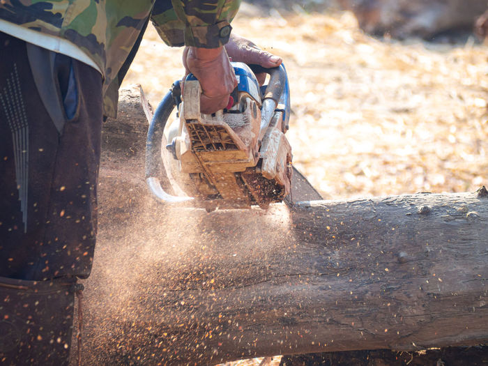 Midsection of man cutting wood outdoors