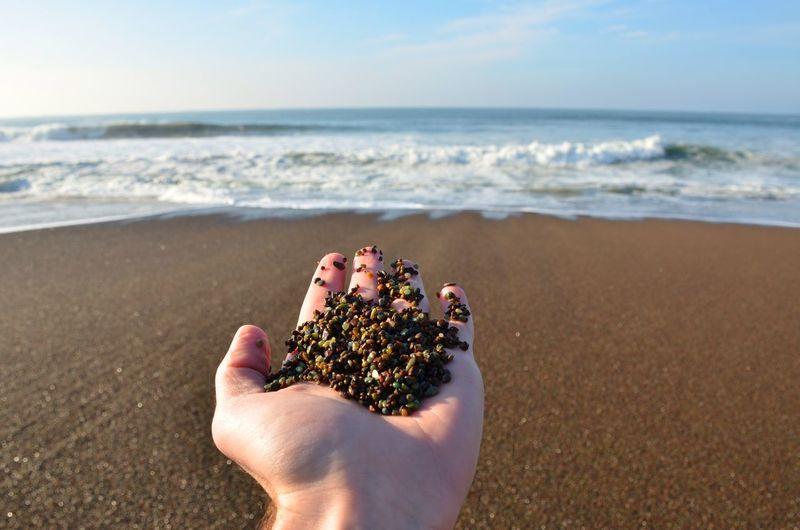 Close-up of hand holding sand on beach