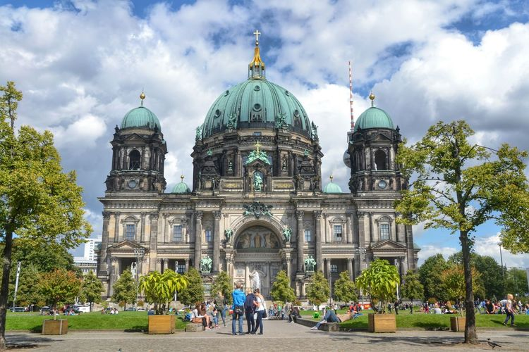 Tourists visiting berlin cathedral against cloudy sky