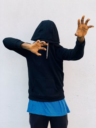 Young man wearing hood gesturing while standing against white background