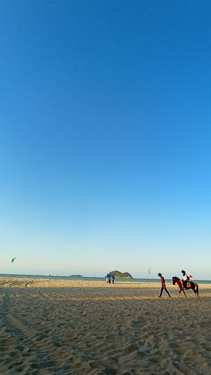 Group of people on beach against clear blue sky