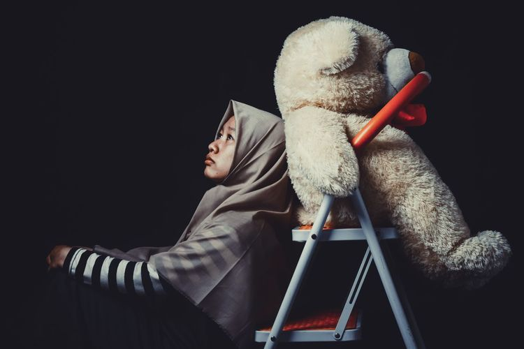 Girl with teddy bear against black background
