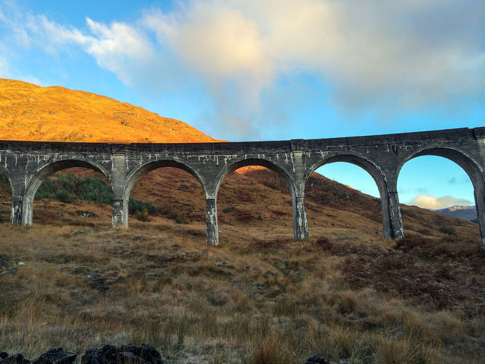 Bracken Harry Potter Harry Potter Viaduct Sunlight Arch Architecture Bridge - Man Made Structure Built Structure Cloud - Sky Connection Day Glenfinnan Nature No People Outdoors Sky Train - Vehicle Transportation Viaduct