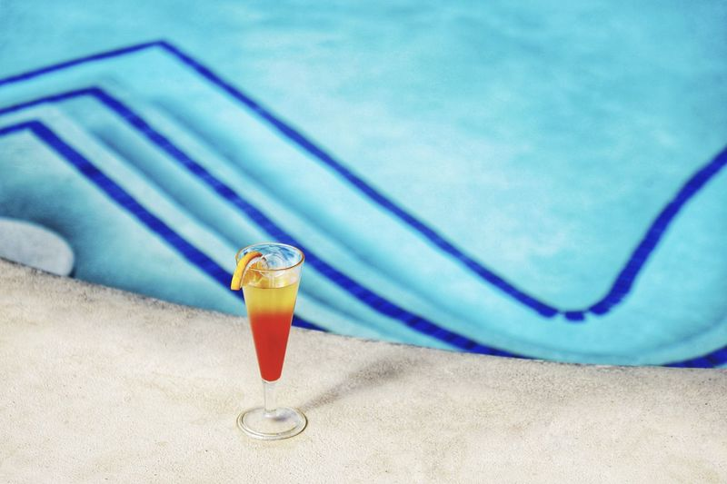 High angle view of drink on table by swimming pool