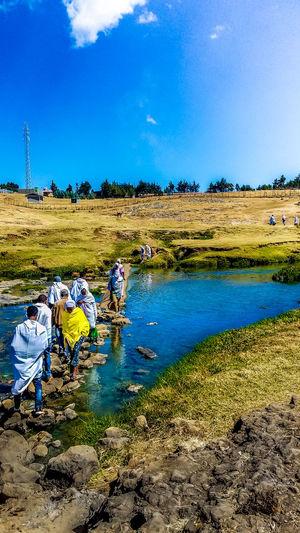 EyeEmNewHere People Crossing River On Rocks Daylight Water Beauty In Nature Rural Scene Sky