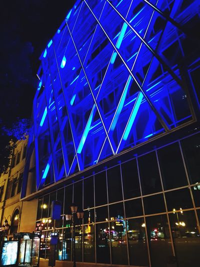 Low angle view of illuminated building against blue sky