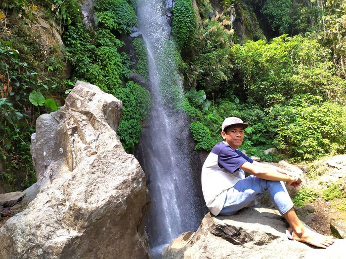 Full length of young man sitting on rock against waterfall