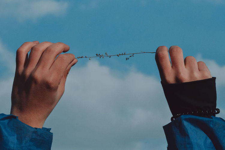 Low section of person holding hands against sky