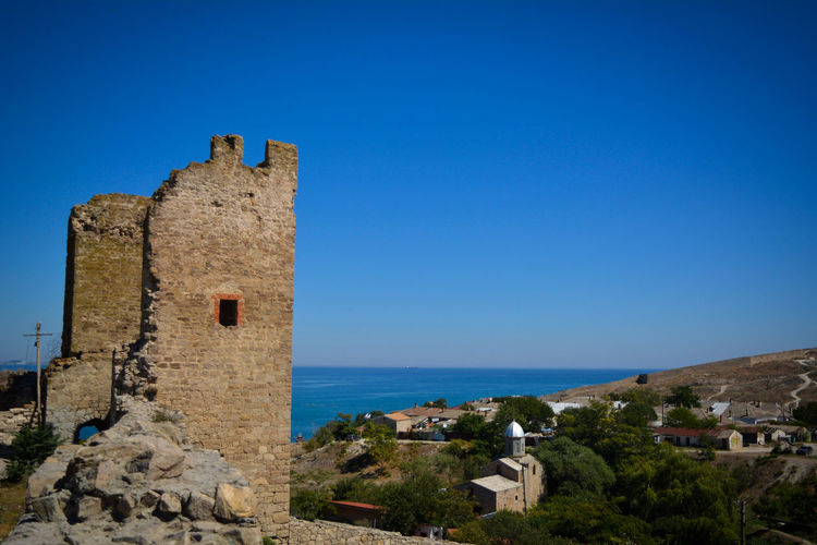Castle by sea against blue sky