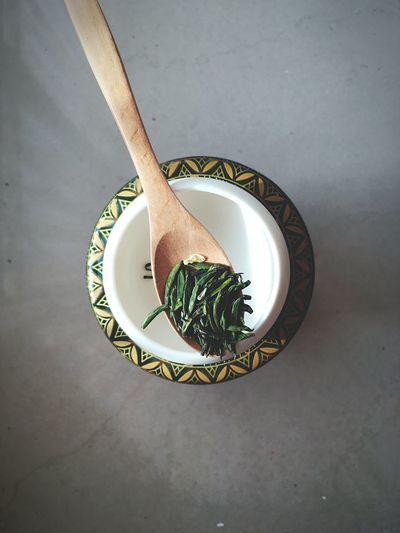 High angle view of herbs in wooden spoon over bowl