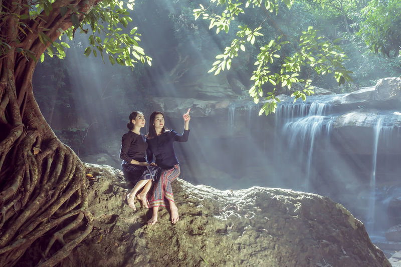 Friends sitting on rock against waterfall in forest
