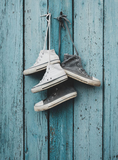 Wood - Material Hanging No People Wall - Building Feature Old Day Security Blue Door Protection Entrance Metal Outdoors Still Life Close-up Rope Textured  Pattern Shoe Sneakers Hanging
