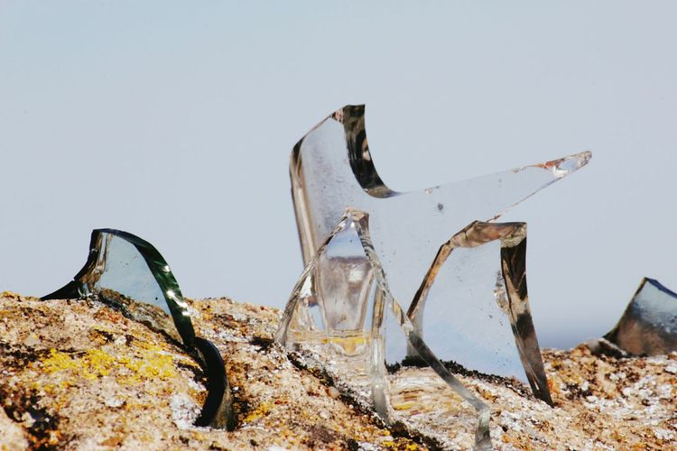 Close-up of glass pieces on surrounding wall against sky