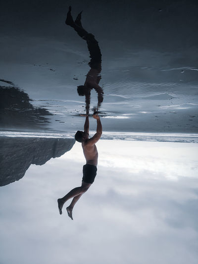Upside down image of man doing handstand at beach