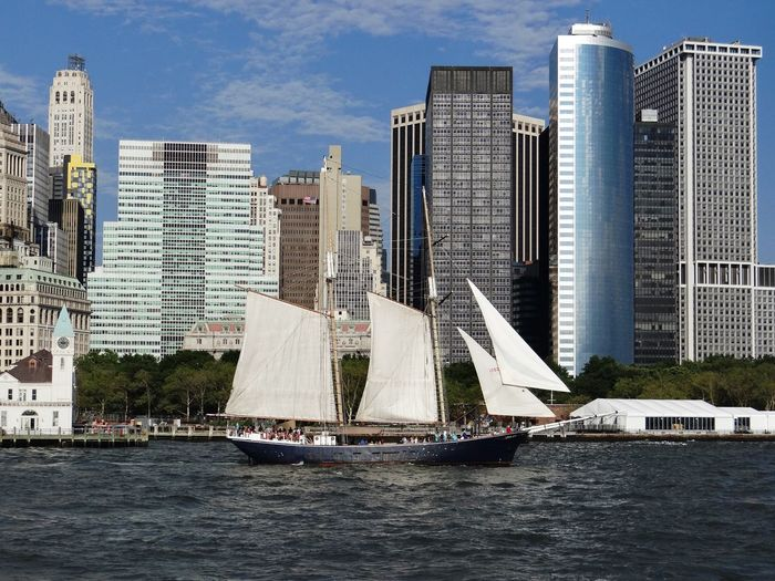 Sailboat on river against financial district