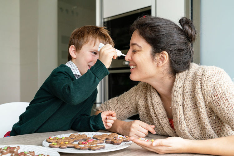 Mother and son preparing food on table at home