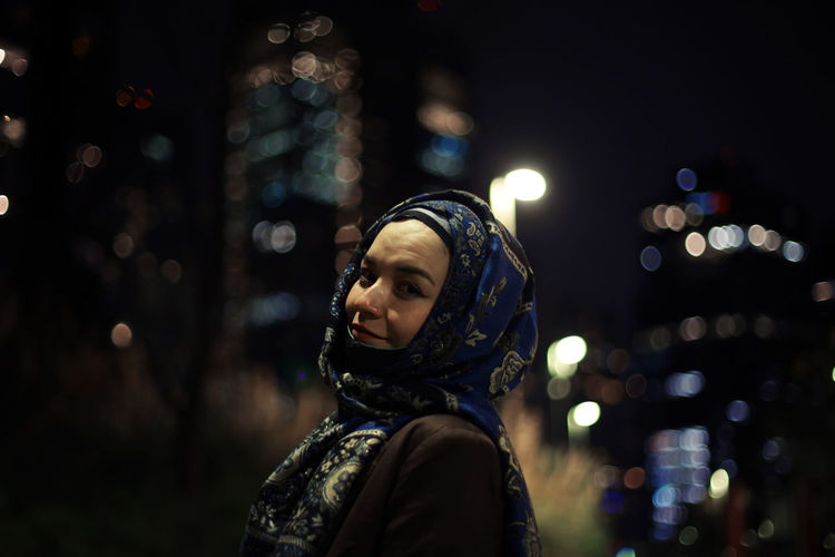 Portrait of woman wearing hijab in city at night