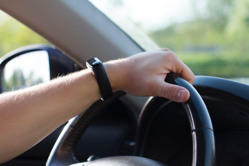 Young man in smart watch driving a car Trip Vacation Sunlight Businessman Leather Roadways Lifestyle Driver Summer Roadtrip Technology Wristwatch Smart Watch Human Hand Car Motor Vehicle One Person Mode Of Transportation Land Vehicle Transportation Vehicle Interior Day Lifestyles Steering Wheel Car Interior