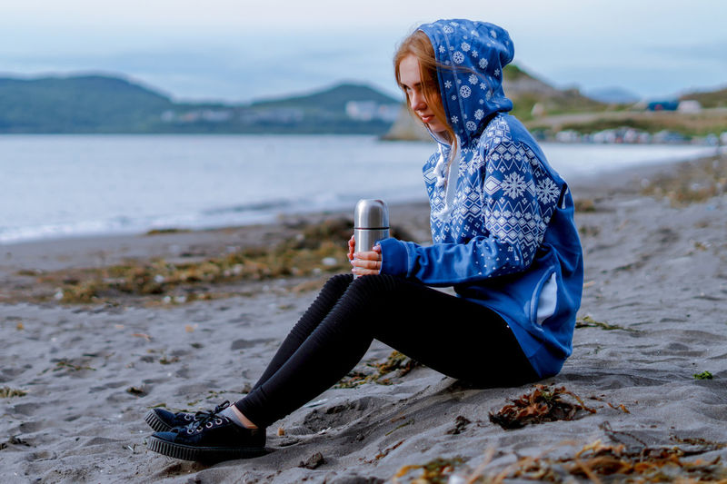 Side view of young woman holding bottle while sitting at beach