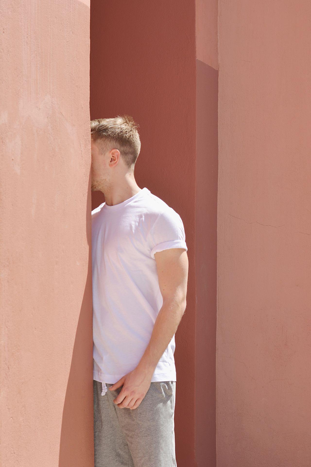 Young man standing by wall