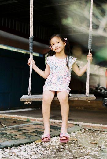 Full length portrait of girl sitting on swing