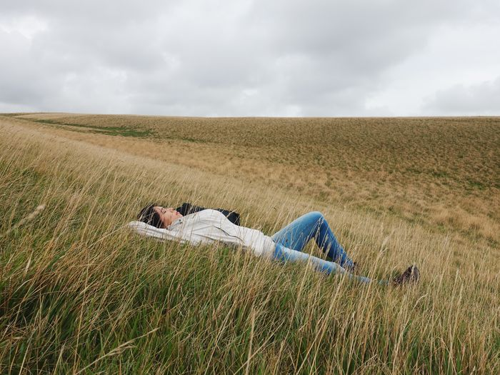 Woman in white jacket lying down on dried grass field against cloudy sky