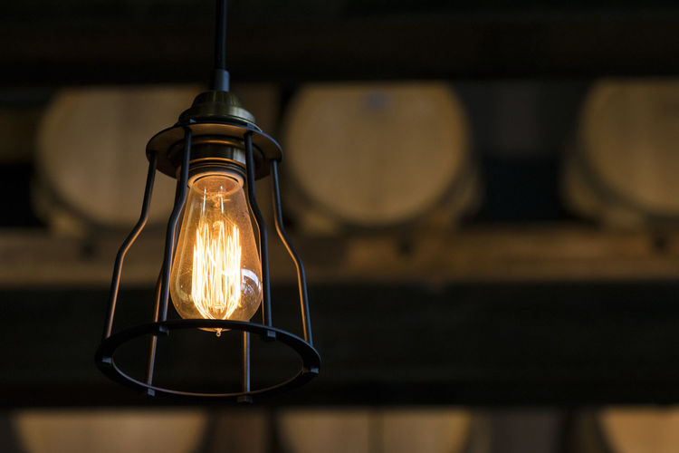 Close-up of illuminated light bulb hanging against barrels in cellar