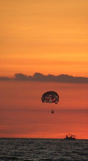Silhouette people parasailing over sea against orange sky
