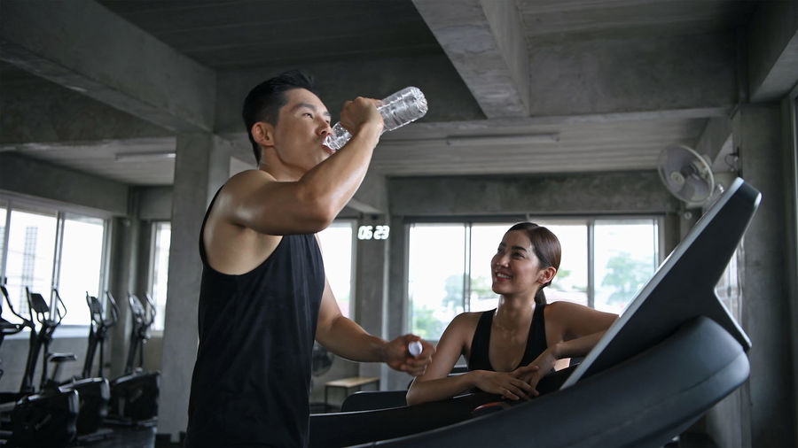 Instructor and woman talking at gym