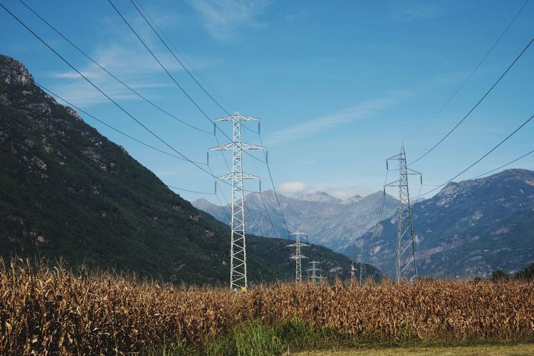 Electricity pylons by mountains against sky