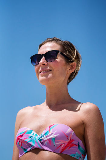 Low angle view woman with short hair enjoying sunshine wearing sunglasses smiling