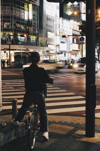 Man riding bicycle on city street at night