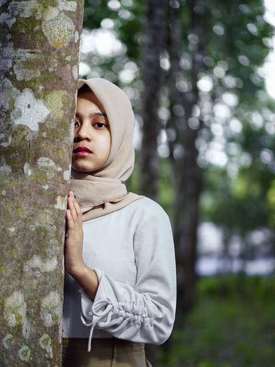 Portrait of teenage girl standing against tree trunk