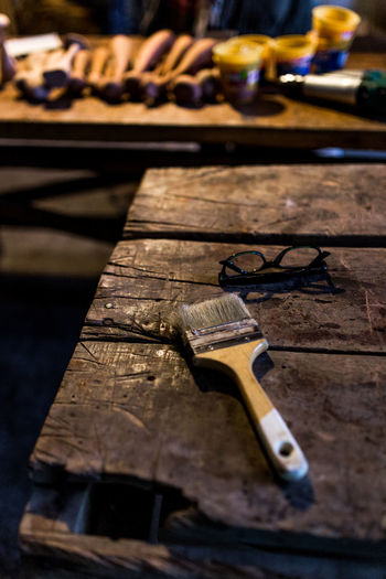 Close-up of paintbrush and eyeglasses on wooden table