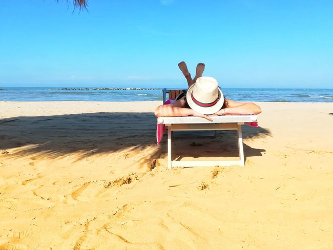 Legs Crossed Travel Summer Paradise Vacation Holidays Sunbathing Woman Lying On The Sunbed Tanning Woman Lying Down Woman Sea Water Clear Sky Beach Full Length Sand Relaxation Summer Seascape Straw Hat Sun Hat Beach Towel Beach Umbrella Lounge Chair Parasol