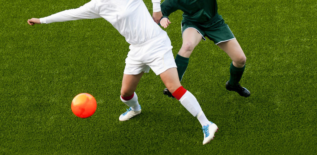 Low section of people playing soccer ball on grass