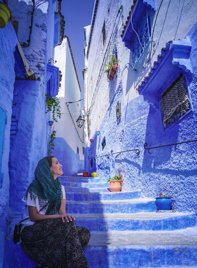 """""""The Blue City"""" - Chefchaouen, Morocco. Chefchaouen Chefchaouen Medina Chefchaouen Blue City MoroccoTrip Morocco Travel Digital Nomad EyeEmNewHere Travelling Tourist Attraction  Tourism Real People Architecture Built Structure One Person Lifestyles Building Exterior Sitting Leisure Activity Day Blue Women Building Adult Young Adult Nature Staircase Full Length Casual Clothing Plant Outdoors"""
